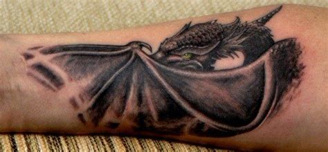 forearm tattoo of a dragon which hides behind his wings