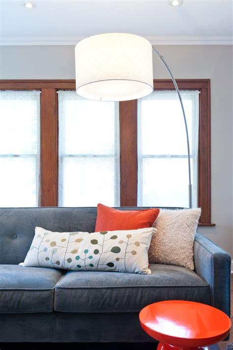 large floor lamp, blue sofa, orange accent stool and