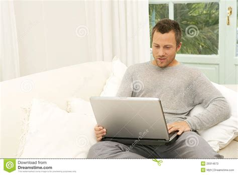 laptop on couch man on couch with laptop at home stock photos image