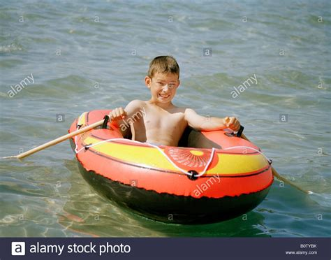 the boys and the boat young boy in an inflatable boat in the sea stock photo