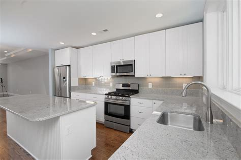 white kitchen cabinets with grey countertops glass subway tiles kitchen grey soft leather sofa dark
