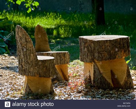 Rustic garden table and chairs carved from an old tree trunk in the stock photo royalty free