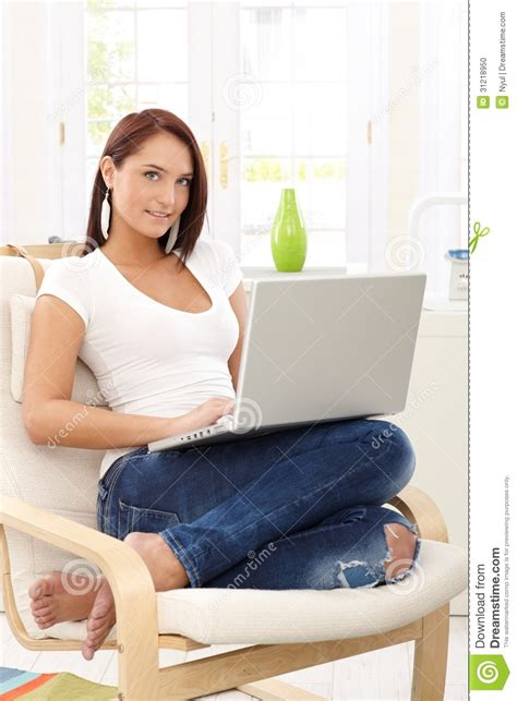 woman in armchair smiling woman in armchair with computer stock photo