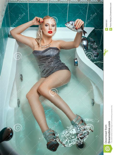 pin up girl in bathtub beautiful woman lying dressed in a bathtub and holding