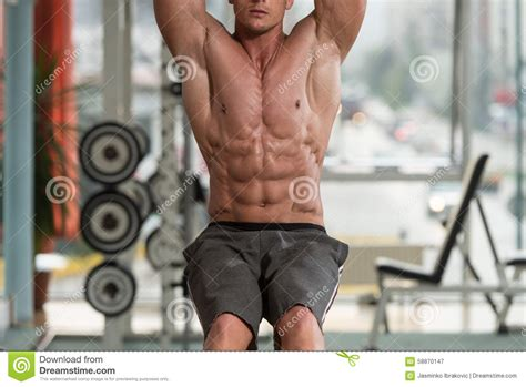 performing hanging leg raises abs exercise stock photo image 58870147