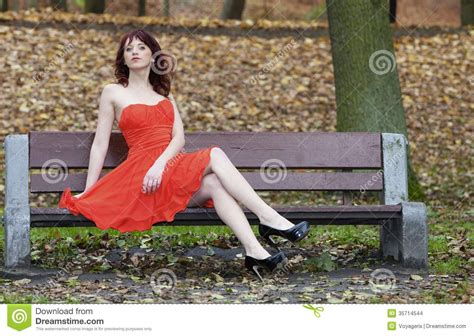 women bench girl in elegant red dress sitting on bench in autumnal