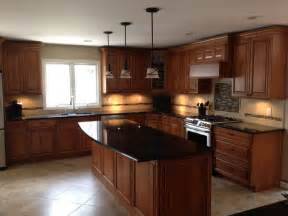 Cherry Wood Kitchen Cabinets With Black Granite Lights Above The Island And Backsplash For The Home