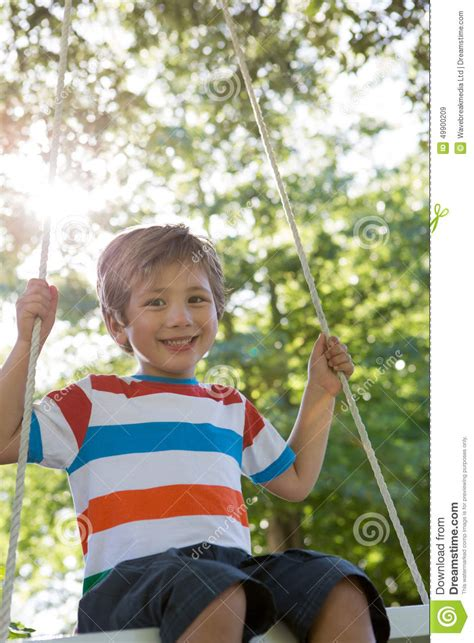 crystal swing happy days happy little boy on a swing in the park stock photo