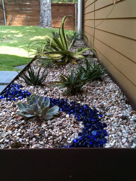 River Rock Planter by Steel Planter With Succulents River Rock And Blue Glass