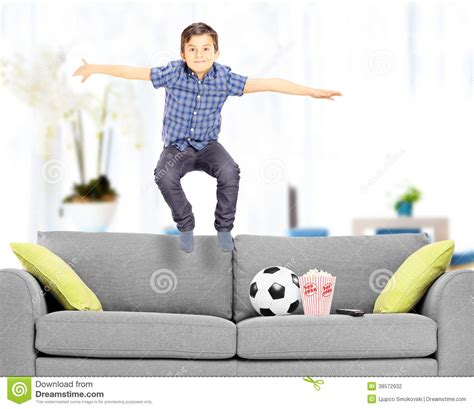 couch jumping overjoyed boy jumping on couch at home stock photo image
