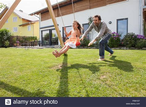 pushing a swing father pushing daughter on a swing in garden stock photo