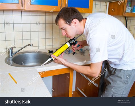 plumber putting silicone sealant installing kitchen stock