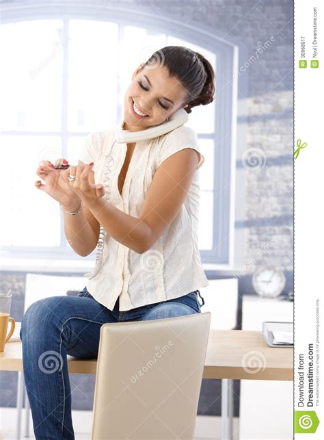 Woman filing nails on phone
