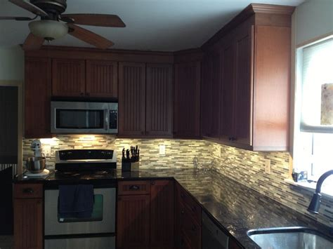 led kitchen backsplash kraftmaid maple cinnamon cabinets with black galaxy