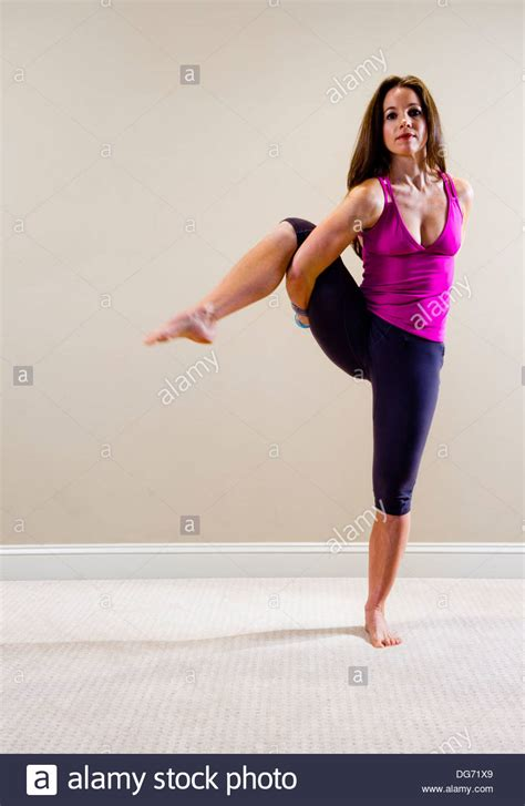 fashion for a 37 year old woman 37 year old brunette woman doing a yoga pose in a home