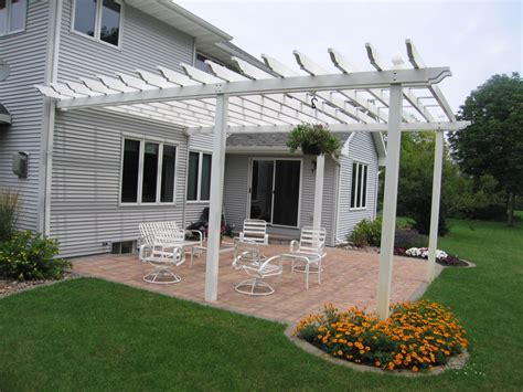 backyard off large white pergola off of the back of a house for a backyard entertainment space the