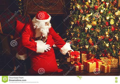 images of christmas tree and santa claus santa claus with gifts around christmas tree stock photo
