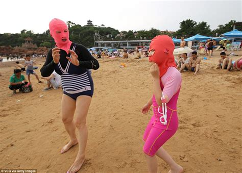 Chinese bathers wear face kini masks when in the sea to protect themselves from the sun daily