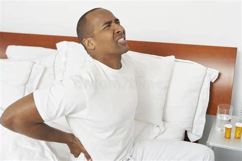 mal di schiena a letto uomo con il mal di schiena a letto fotografia stock