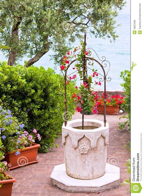 giardini in fiore foto giardino di fiore con il pozzo della pietra fotografia