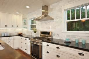 white kitchen with wood island carrara backsplash black