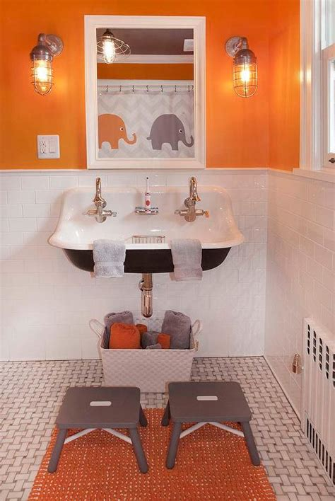 grey orange bathroom cottage mudroom with black trough sink and three faucets