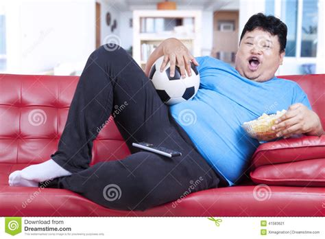 fat guy on couch fat man watching football match at home stock photo