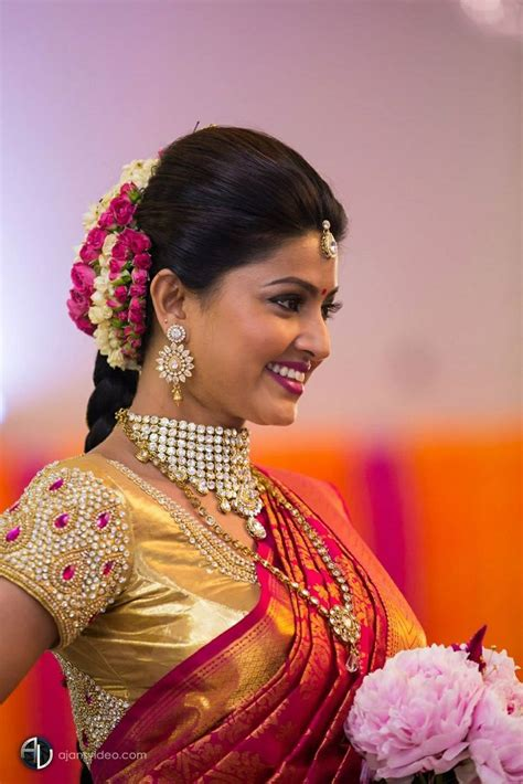 hairstyles for saree in indian wedding traditional southern indian bride wearing bridal saree