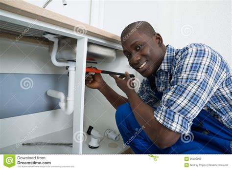 male plumber fixing pipe  sink stock photo image