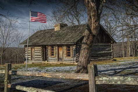 log cabin outpost in missouri with american flag