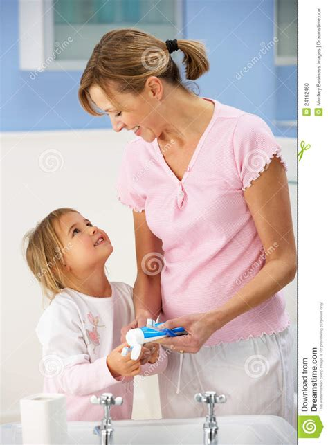 mom bathroom mother and daughter cleaning teeth in bathroom stock photo