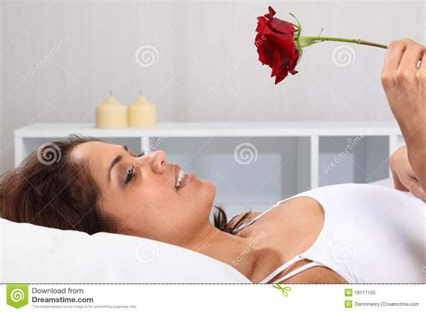 cama holdings beautiful happy woman in bed holding a red rose royalty