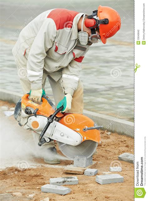 construction workers haircut builder worker cutting curb with disc saw stock photo