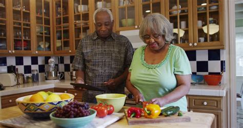 Black Cooking In The Kitchen by Senior American Enjoying Healthy Meal Stock