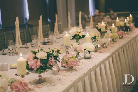 top table flowers at the mere silver mercury glass vases and pillar candles flowers by
