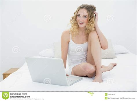 sitting in bed pretty happy blonde sitting on bed using laptop stock