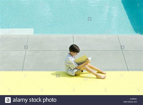 Best Books For Pool Side Reading by Boy Sitting Next To Swimming Pool Reading Book High