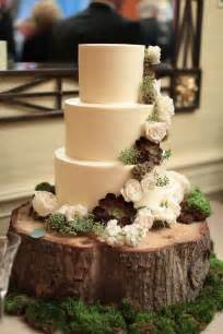 gorgeous rustic all white cake with sage and white flowers on a tree stump with moss wedding
