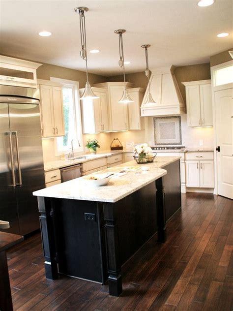Dark Wood Floors with cream cabinets and dark island