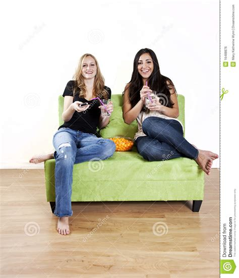 two girls having on couch girls watching tv laughing royalty free stock image