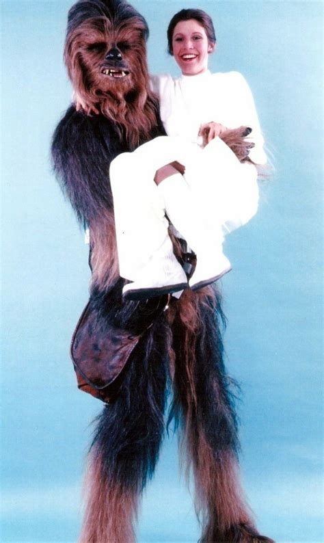 actress lifting and carrying actor chewbacca and princess leia carrie fisher star wars