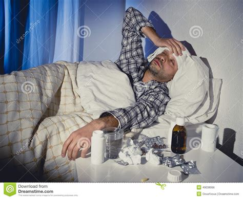 bed medicine sick man lying in bed with headache suffering cold and