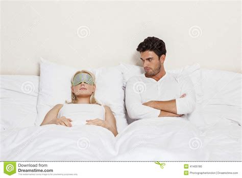 how to be good in bed for women angry young man looking at woman sleeping in bed stock