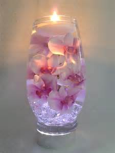 pink orchids with purple centers float in a 12 inch glass vase