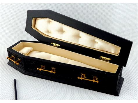 black doll in a coffin carved black coffin with gold handles wooden jbm furniture