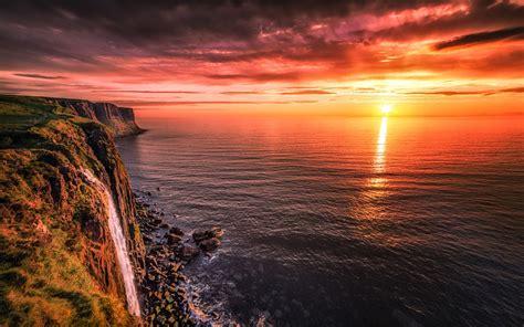 sea shore rock ocean horizon red sky  rays  sun