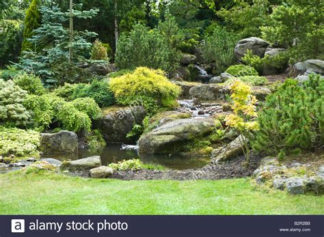rock garden with pond waterfall shrubs and trees in