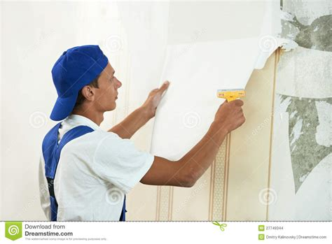 Home Interior Decorator painter worker peeling off wallpaper stock images image