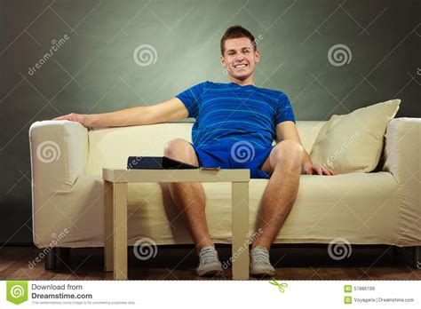 laying on a couch young man relaxing on couch stock photo image 57886199