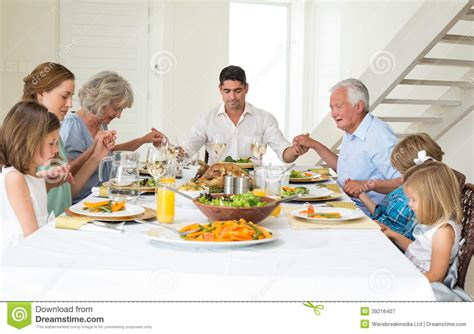 imagenes de la familia rezando family praying together before meal at dining table stock